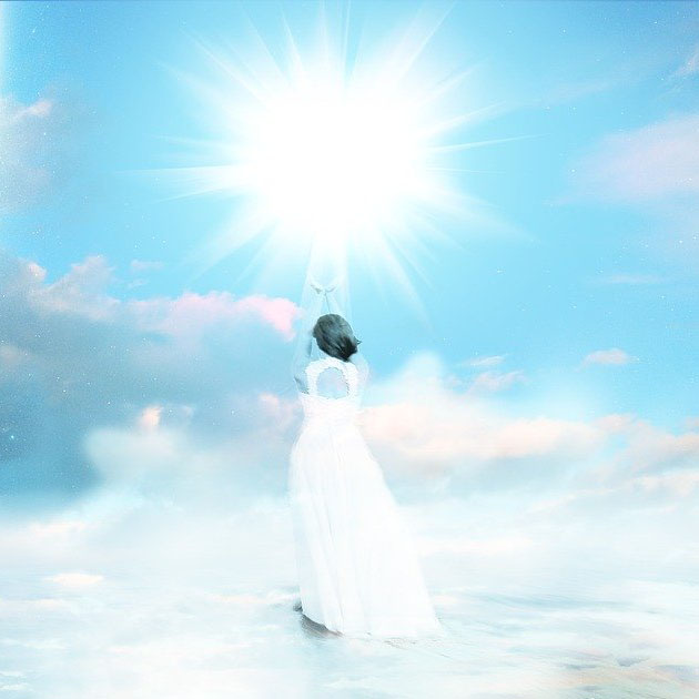 Woman reaching toward a light in the sky